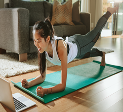 Asian women completing a home workout on a yoga mat in her living room whilst looking at her laptop